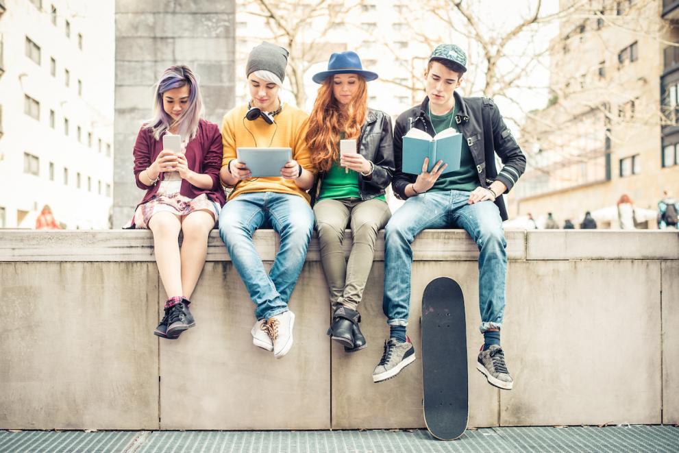 Ungdomar sitter på en mur och läser