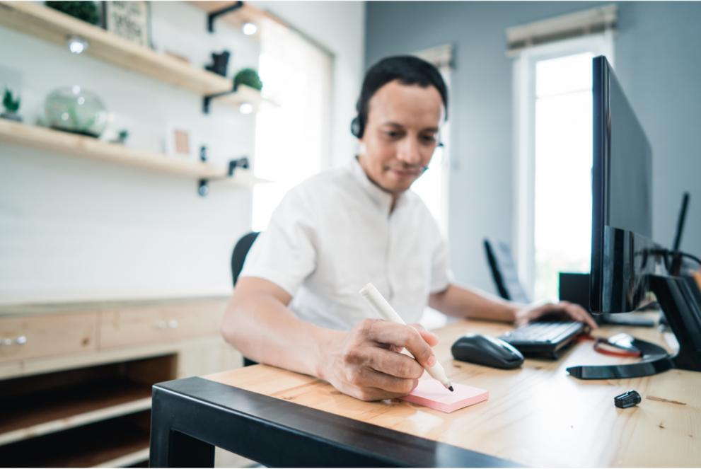 Man sitter vid ett skrivbord med dator och block framför sig som han skriver i.